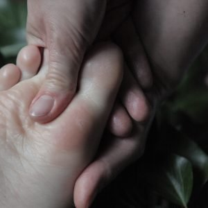 dłonie masażyści obejmujące stopę klienta